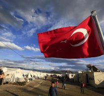 FILE - In this Wednesday, March 16, 2016 file photo a Turkish flag flies at the refugee camp for Syrian refugees in Islahiye, Gaziantep province, southeastern Turkey.  German Chancellor Angela Merkel and top European Union officials plan to travel close to Turkey's border with Syria in hopes of promoting a troubled month-old agreement to manage a refugee crisis that has left hundreds of thousands stranded on the migrant trail to Europe. (AP Photo/Lefteris Pitarakis, File)